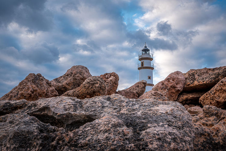 Low angle view of rocks and lighthouse against sky