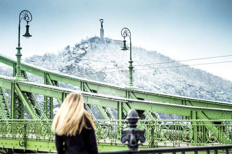 Rear view of woman on bridge against sky in city