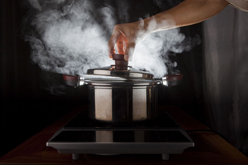 Cropped image of hand opening lid of pressure cooker in kitchen