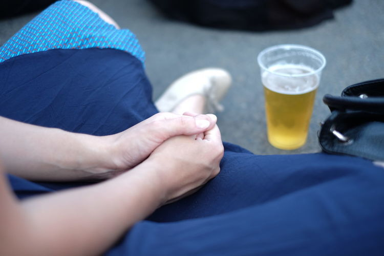 Cropped Image Of Woman Sitting By Beer Glass On Floor