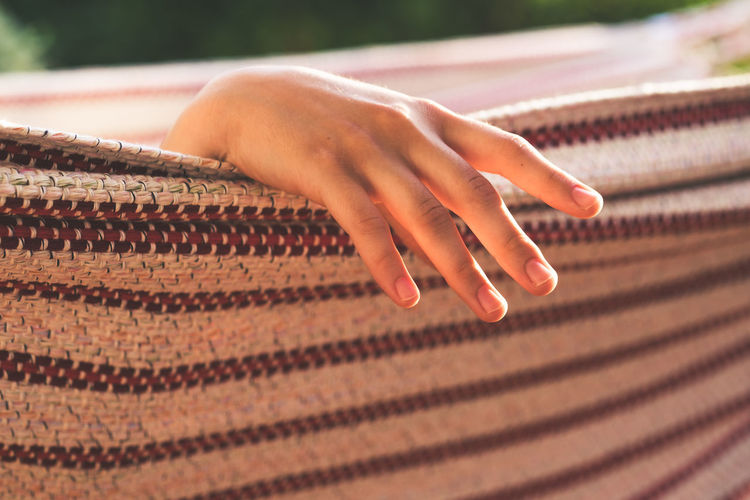 Cropped hand relaxing on hammock