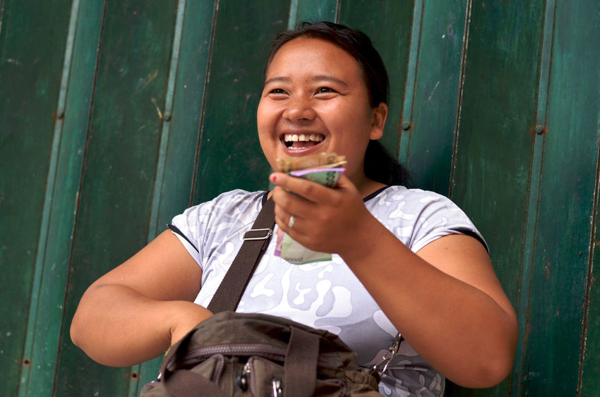 Balinese Balinese Woman Casual Clothing Day Front View Green Happiness Leisure Activity Lifestyles Making Money Money Outdoors Person Portrait Smiling Toothy Smile Woman
