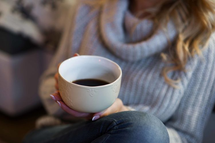 Beautiful woman holding coffee cup in cozy mountain cabin