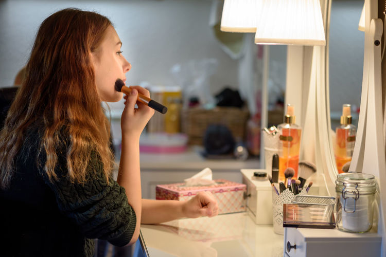 Side view of woman applying make-up in front of mirror at home