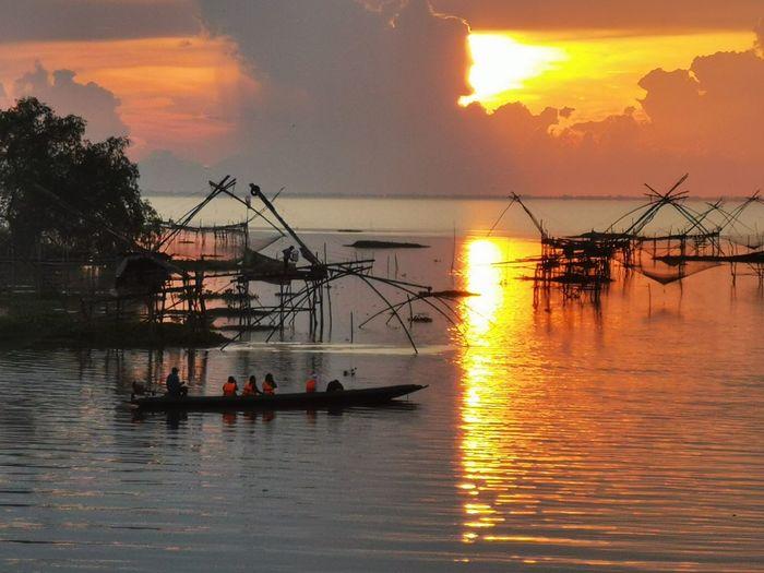 Silhouette people fishing in sea against orange sky