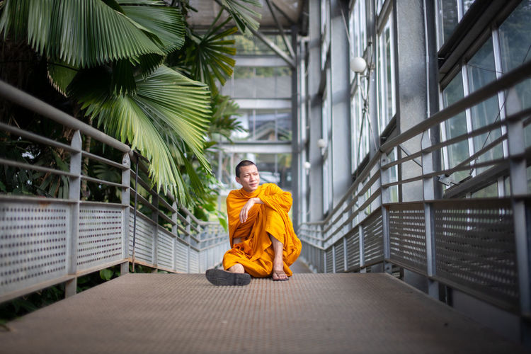 Full length of monk sitting on footpath