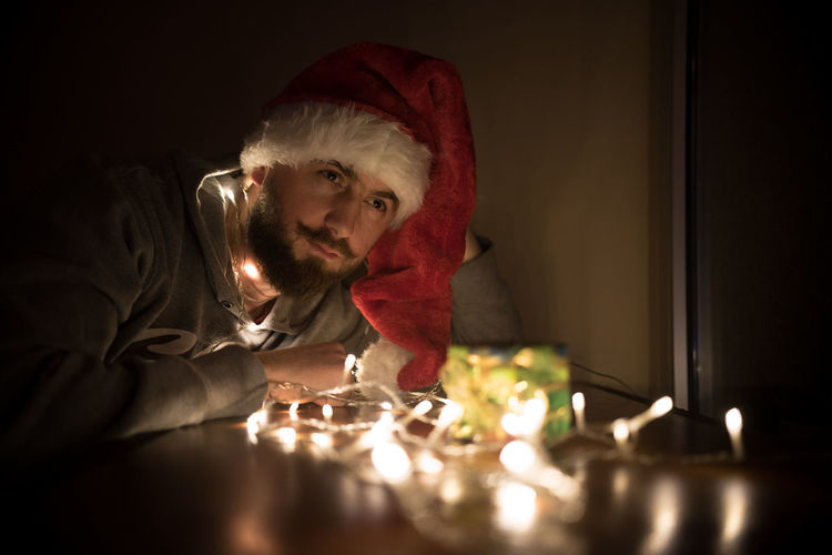 Close-up of young man by illuminated christmas lights on gift in darkroom