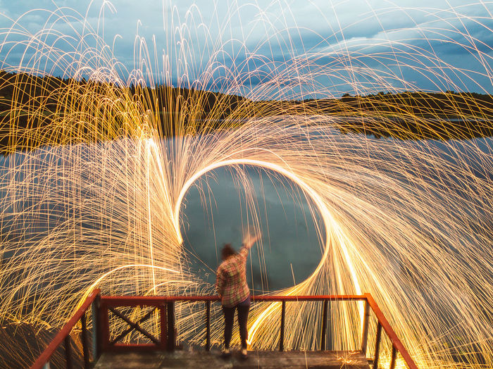 Full Length Rear View Of Woman Spinning Wire Wool By Lake During Dusk