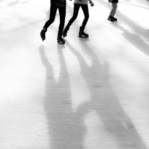 Low section of people ice-skating at rink