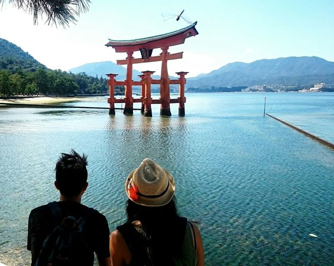 Rear View Of Man And Woman Looking At Torii Gate Amidst River In Itsukushima Shrine