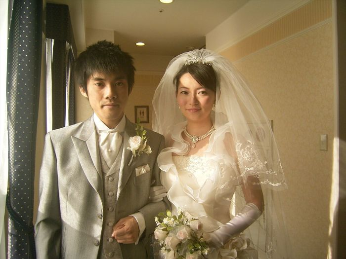 Portrait of smiling bride and groom standing by window