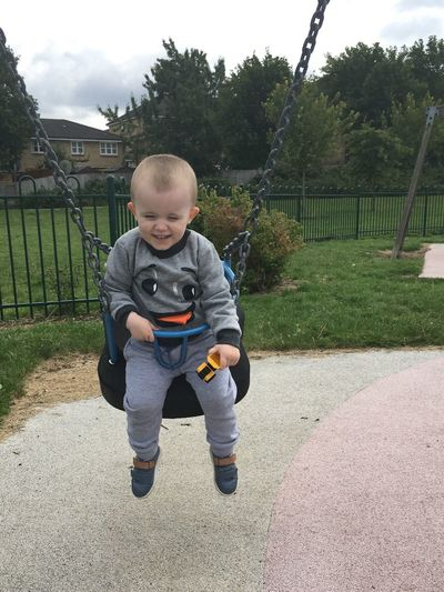 Playful baby boy sitting on swing at park