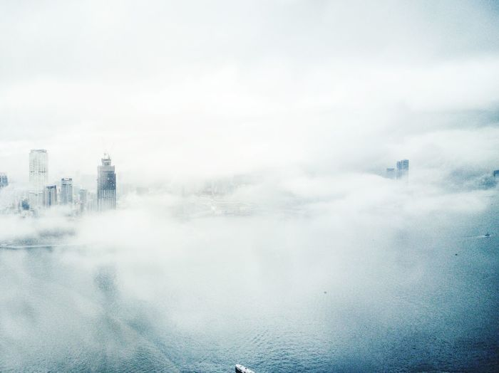 Calm misty river with buildings in distance