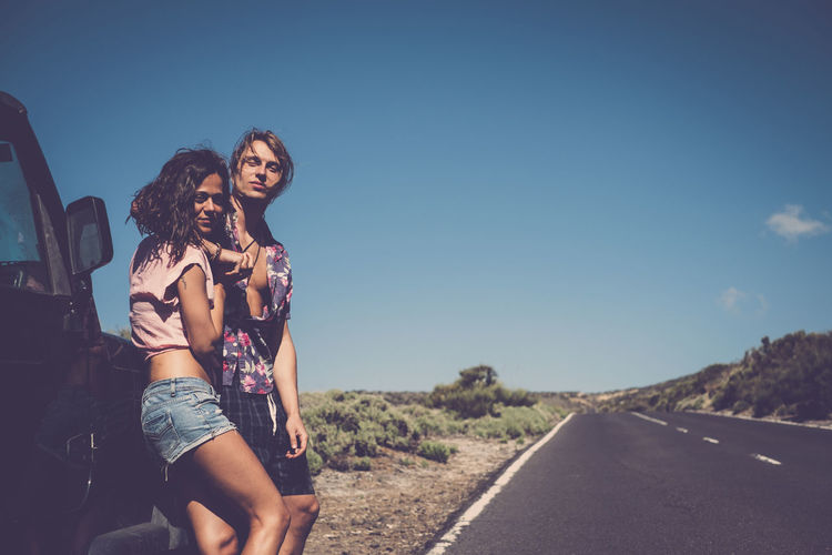 Portrait of young couple standing on road against sky during sunny day