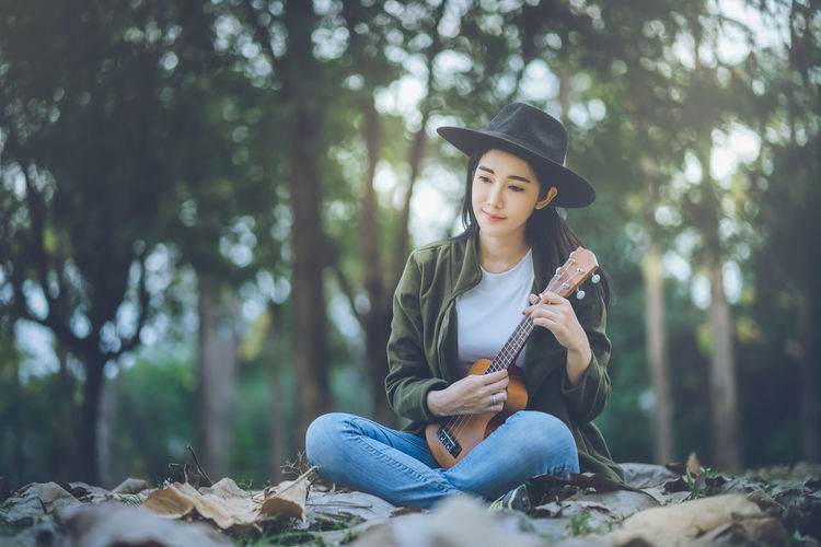 Asian woman playing ukulele in the garden One Person Musical Instrument Young Adult Tree Real People String Instrument Leisure Activity Plant Holding Front View Sitting Land Lifestyles Musical Instrument String Young Women Casual Clothing Forest Music Musical Equipment Day Musician Acoustic Guitar Outdoors Plucking An Instrument Beautiful Woman