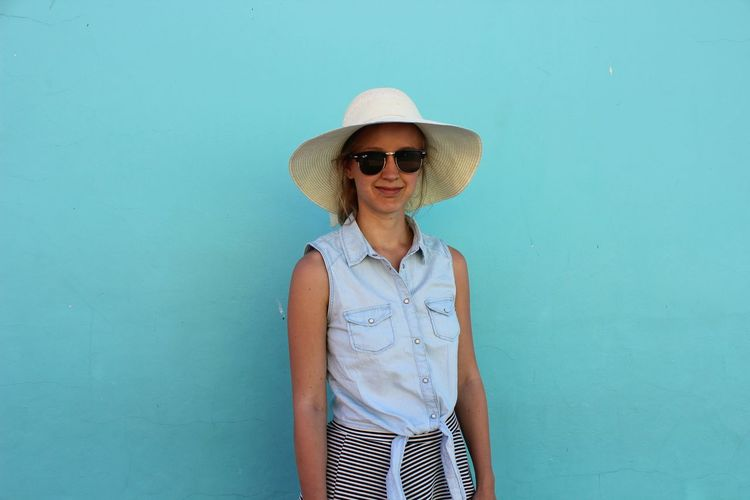 Portrait of young woman wearing hat against wall