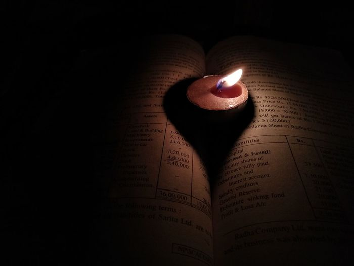 Close-up of lit candles on book in darkroom