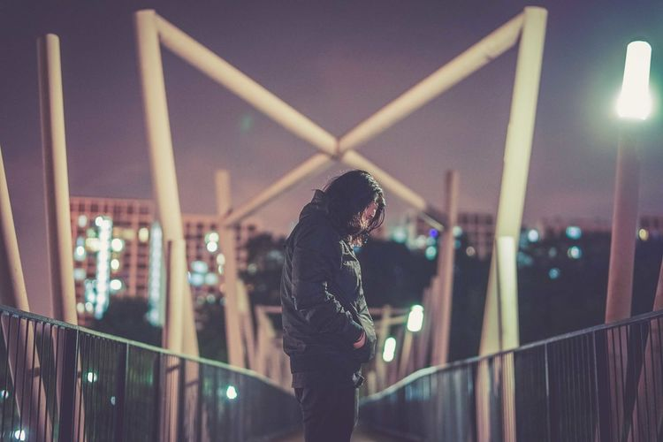 Side view of man standing on footbridge against illuminated city at night