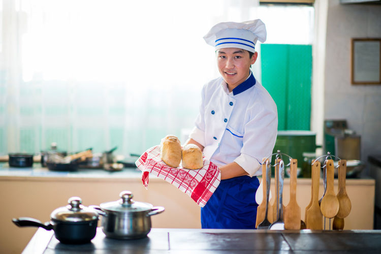 The Modern Professional Occupation One Person Looking At Camera Uniform Holding Smiling Food And Drink Portrait Indoors  Clothing Food Standing Emotion Real People Happiness Kitchen Preparation  Preparing Food Chef Three Quarter Length Waist Up Side View Kyrgyzstan
