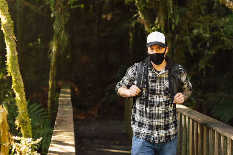 Portrait of man wearing mask standing in forest