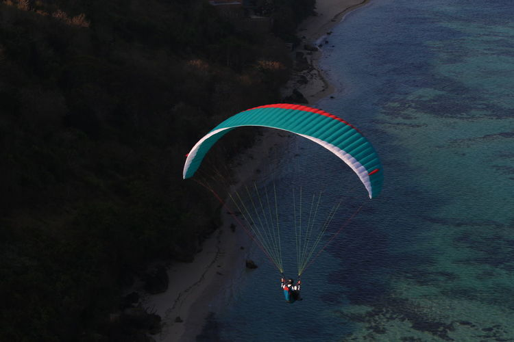 Person paragliding over water