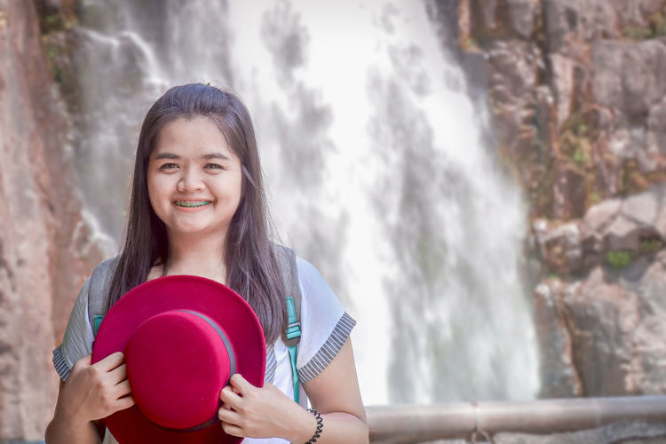 Portrait Of Smiling Young Woman With Hat Standing Against Waterfall