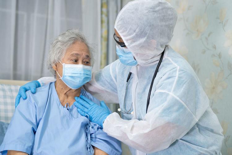 Doctor wearing hazmat suit consoling patient at hospital