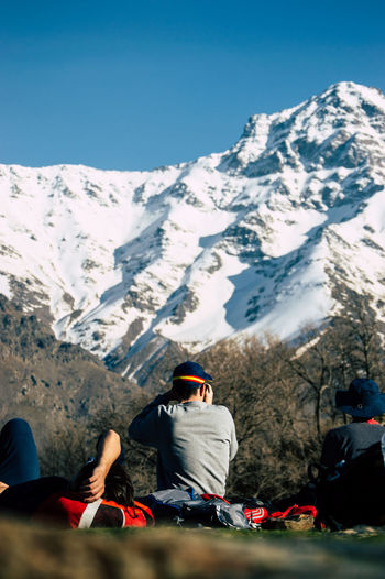People sitting on snowcapped mountain against sky