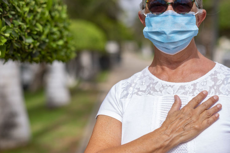 Midsection of woman wearing mask standing outdoors