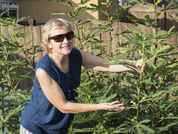 Mature woman wearing sunglasses standing by plants