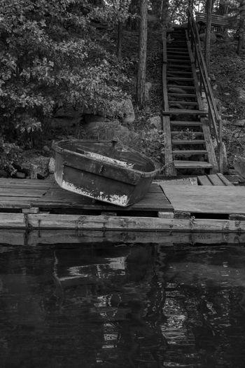 Abandoned boat moored on lake