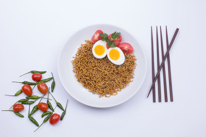 Fried noodle on a white plate styled beautifully Noodles Breakfast Eating Utensil Egg Food Food And Drink Fork Freshness Friednoodle Healthy Eating High Angle View Indoors  Kitchen Utensil Meal No People Noodle Plate Ready-to-eat Still Life Studio Shot Tomato Vegetable Wellbeing White Background