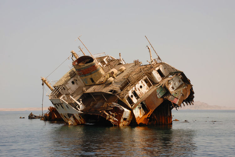 Abandoned ship in sea against clear sky