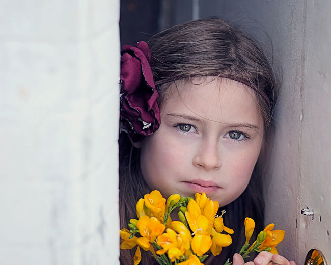 Close-up portrait of girl with yellow flowers
