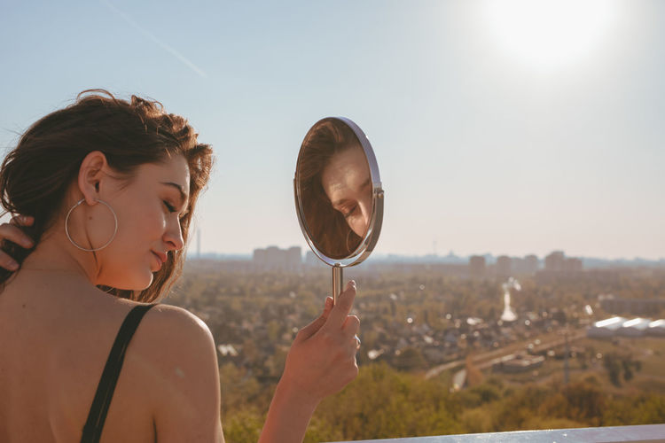 Rear view of young woman with mirror standing against clear sky