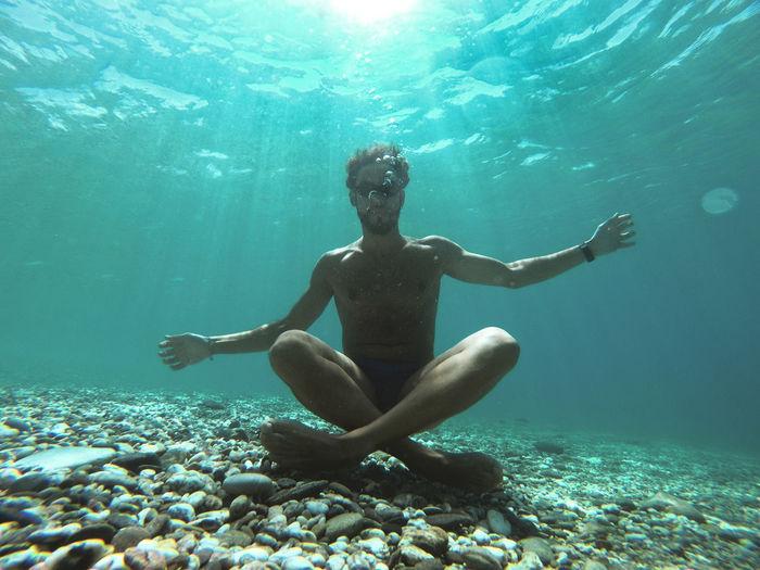 Portrait of shirtless man sitting undersea
