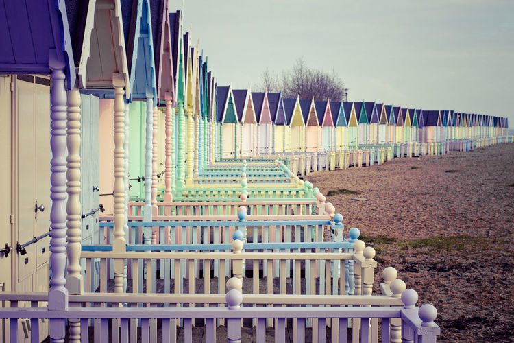 A view of typical English style colourful beach huts on the island of West Mersea in the UK. Sky In A Row Day No People Nature Architecture Built Structure Land Barrier Fence Plant Building Exterior Wood - Material Outdoors Field Railing Absence Repetition Tree West Mersea British Beach Colourful United Kingdom English Culture