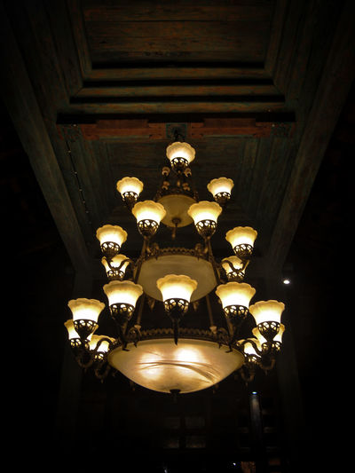 Low angle view of illuminated pendant lights hanging from ceiling in building