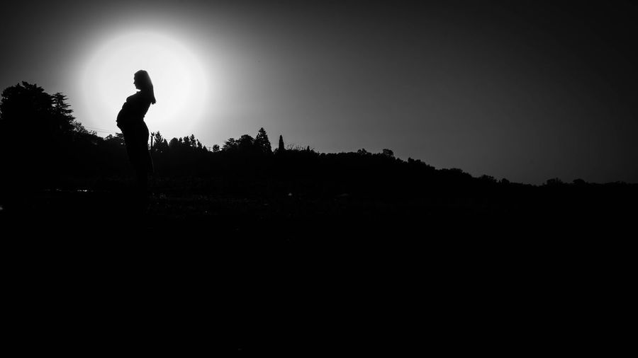 Silhouette man standing on field against clear sky