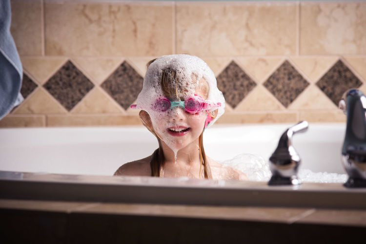 Goggles Bathroom Bathtub Beautiful Woman Bubble Bath Childhood Close-up Day Domestic Bathroom Domestic Room Elementary Age Girl Happiness Headshot Hygiene Indoors  Leisure Activity Lifestyles One Person People Real People Shower Taking A Bath Washing Water Wet Young Adult