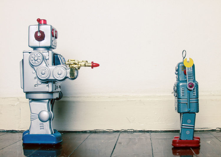 Close-up of robots on floor by wall