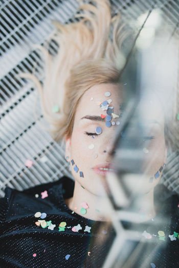 High angle view of woman with confetti on face lying on floor