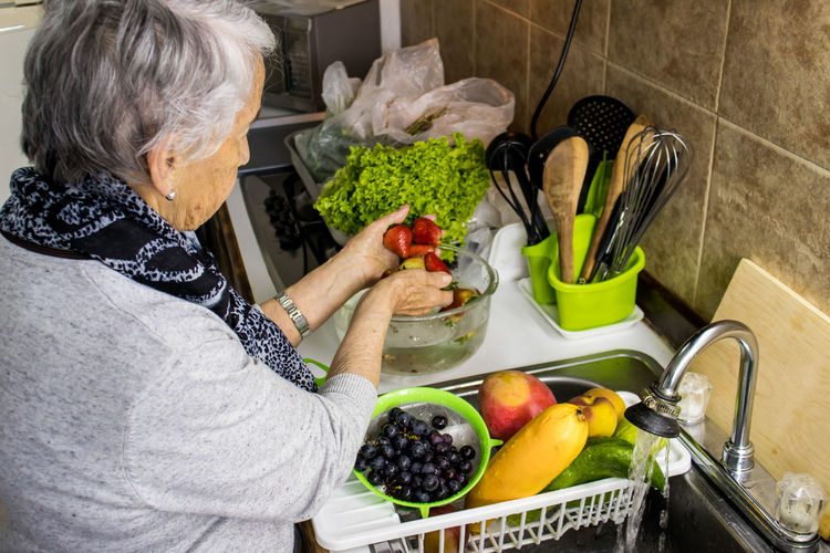 Midsection of woman having food at home