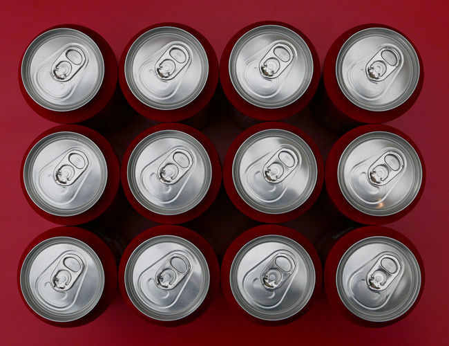 High angle view of drink cans arranged on red table
