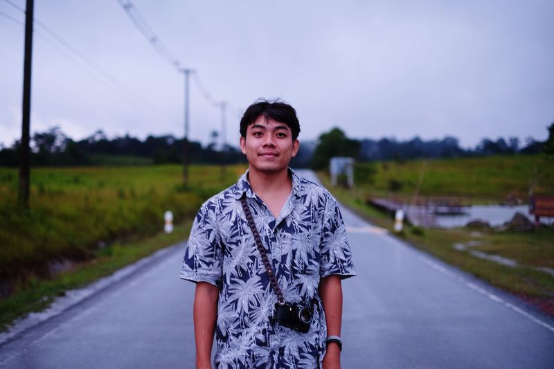 Portrait Of Smiling Man Standing On Road Against Sky