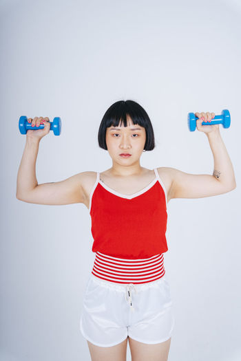 Young woman exercising with dumbbell against gray background