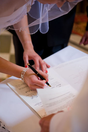 Close-up of bride signing on paper with groom on table