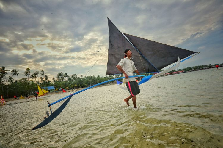 Full length of man with multihull sailboat at beach against cloudy sky