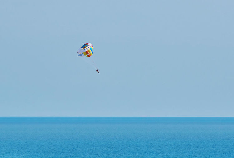 Kite flying over sea against clear sky