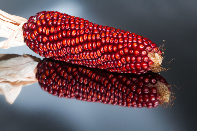 High angle view of red corn on reflection over glass